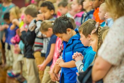 Elementary-age students at Nampa Christian Schools pray together at chapel